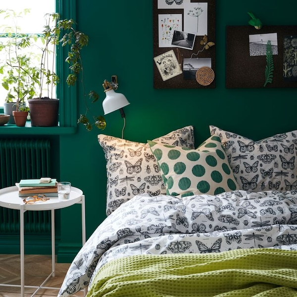 A close up of a bed with SOMMARMALVA bed linen and green ÅSATILDA cushions.