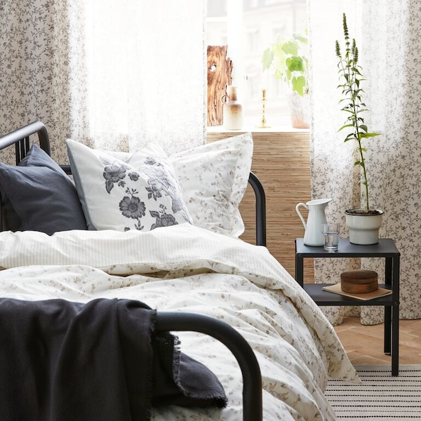 A close up of a bed with STRANDFÄRNE and PRAKTBRÄCKA floral print textiles, ODDRUN cotton throw and a VIGDIS cushion.