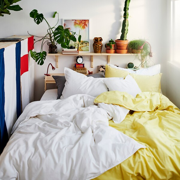 A close up of a bed with white and yellow bedding, a shelf of plants on the wall above.