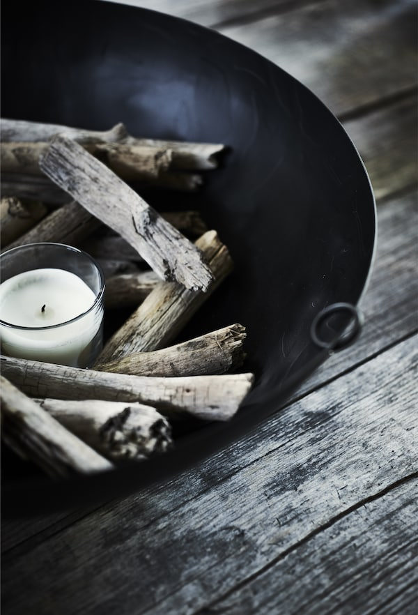 A close-up of a black bowl decorated with a white candle in a glass and wooden sticks.