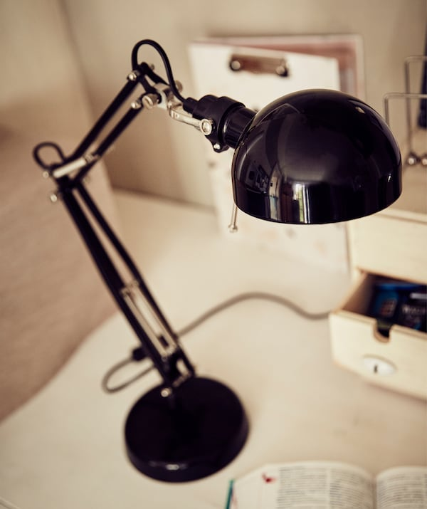 A close-up of a black lamp on a white desk.