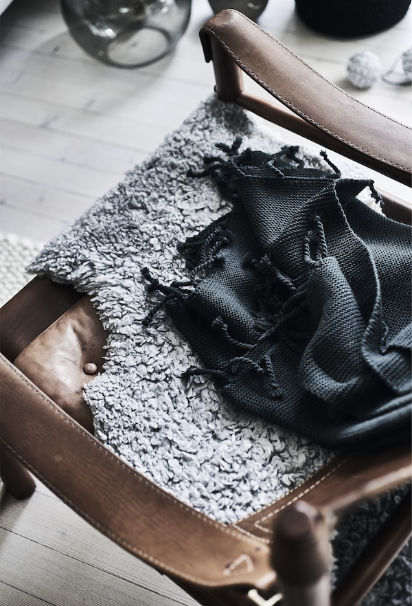 A close-up of a black throw and grey sheepskin draped over a brown leather armchair.