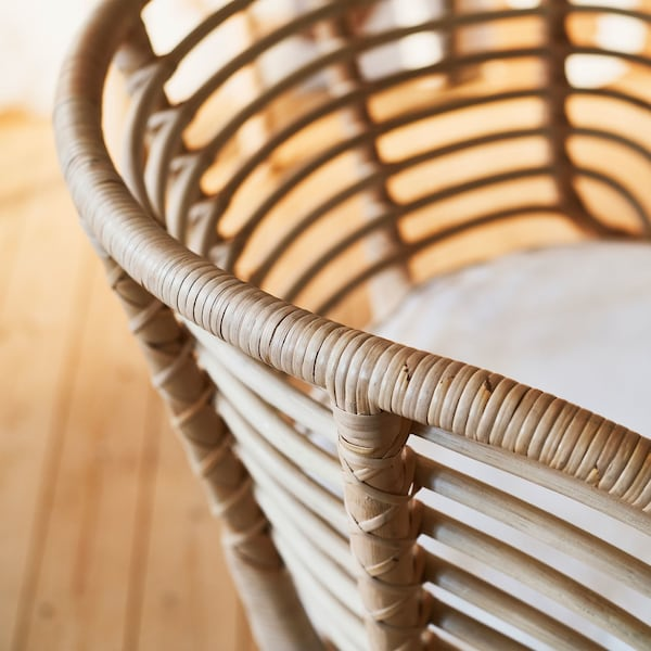 A close-up of a BUSKBO rattan armchair with an airy, curved backrest with widely spaced horizontal supports.