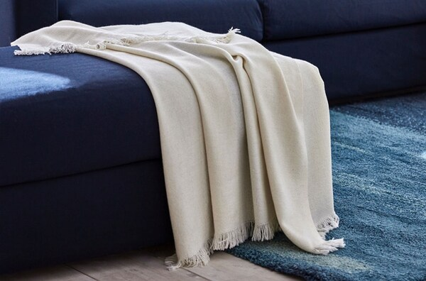 A close up of a cream, ODDRUN throw draped over the edge of a blue sofa.