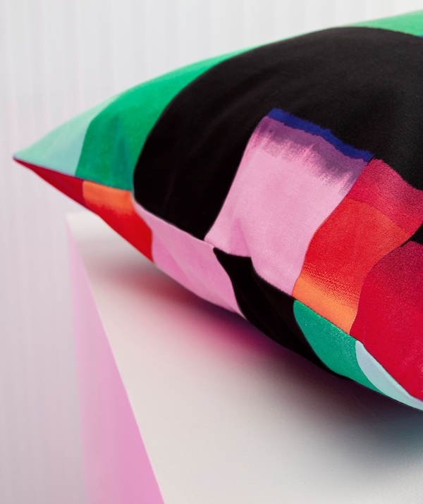 A close-up of a cushion with a multicolour pattern.