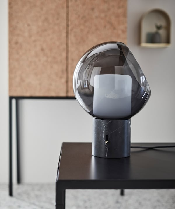 A close-up of a dark grey EVEDAL table lamp with globe shape.