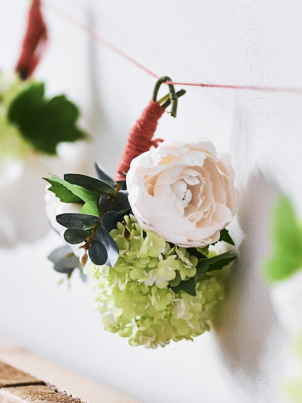 A close up of a floral arrangement hung along a wall