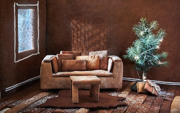 A close-up of a gingerbread house living room with an IKEA sofa, table, rug, small Christmas tree and presents