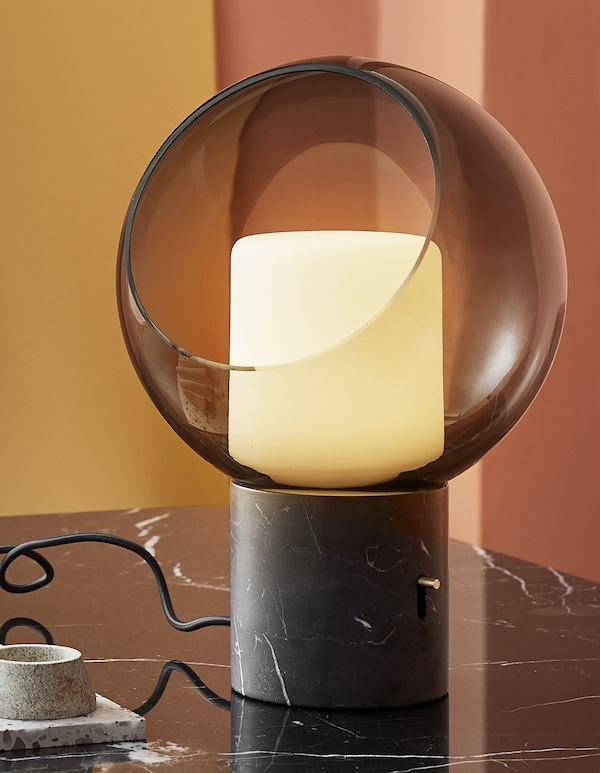 A close-up of a glass globe table lamp with marble base.