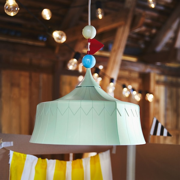 A close-up of a green TROLLBO pendant lamp, designed to look like a circus tent and with cord decorations.