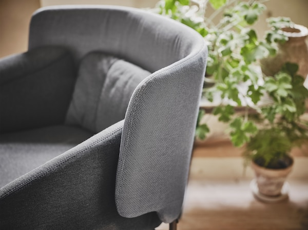 A close-up of a grey low back BINGSTA armchair featuring curved armrests and an enclosing back panel.