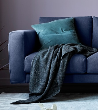 A close up of a grey sofa with a throw and cushion