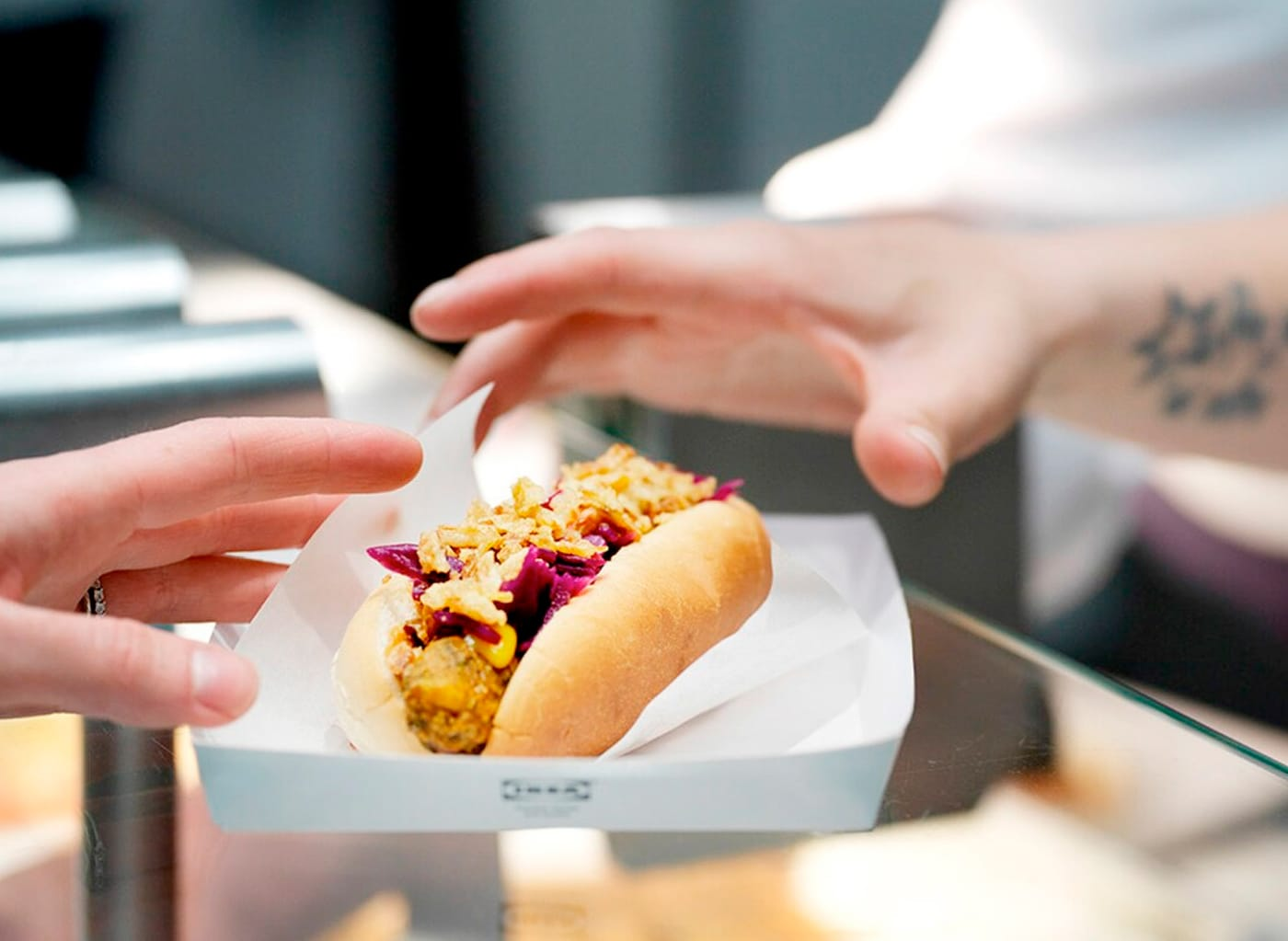 A close-up of a hand reaching for the IKEA veggie hot dog.