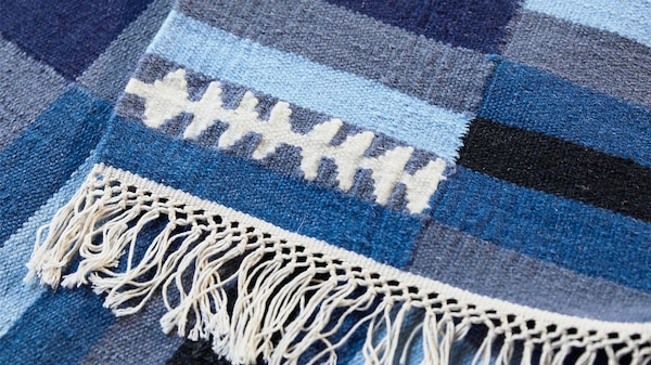 A close-up of a handmade striped TRANGET wool rug in white, black, grey and blue, with white tassels on the edge.