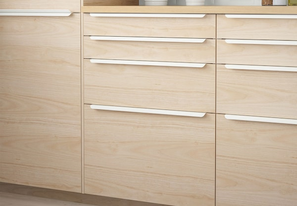 A close up of a kitchen cabinet with IKEA ASKERSUND drawers.