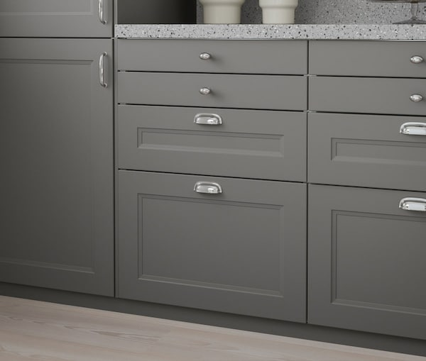 A close up of a kitchen cabinet with IKEA AXSTAD grey drawers.