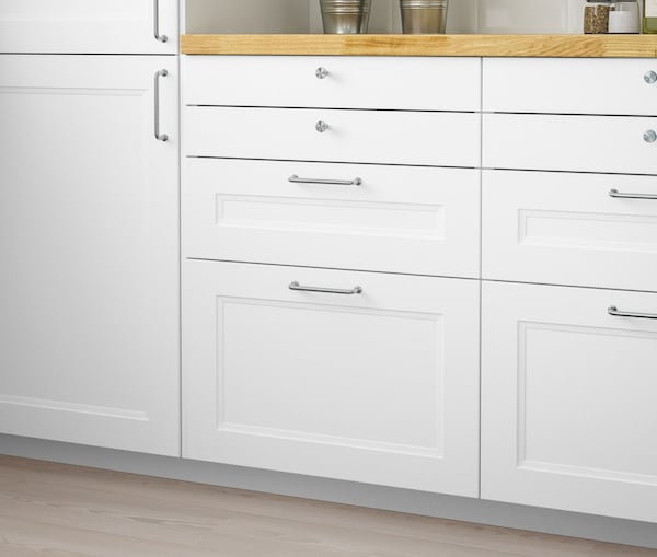 A close up of a kitchen cabinet with IKEA AXSTAD white drawers.