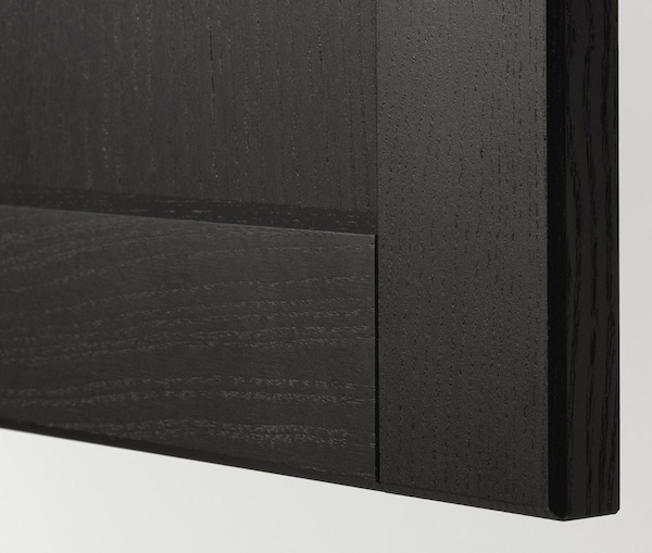 A close up of a kitchen cabinet with IKEA LERHYTTAN black stained doors.