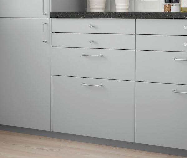 A close up of a kitchen cabinet with IKEA VEDDINGE grey drawers.