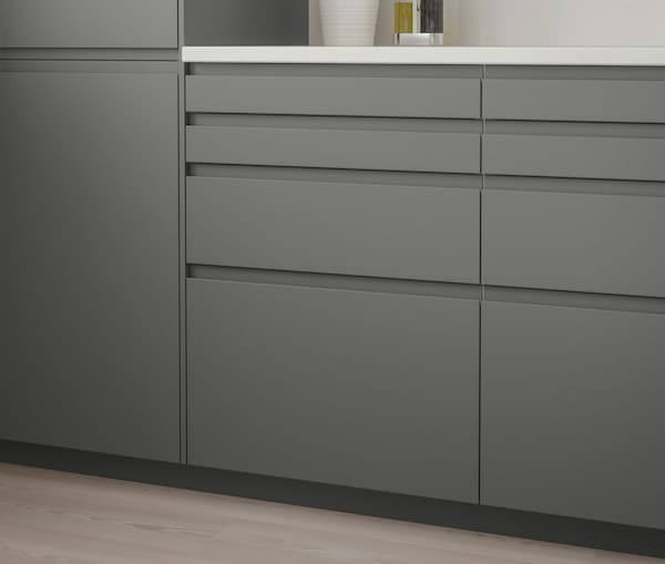 A close up of a kitchen cabinet with IKEA VOXTORP dark grey drawers.
