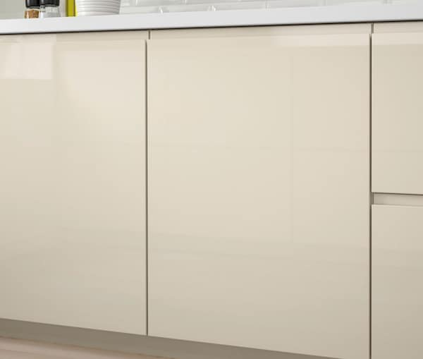 A close up of a kitchen cabinet with IKEA VOXTORP high-gloss light beige doors.