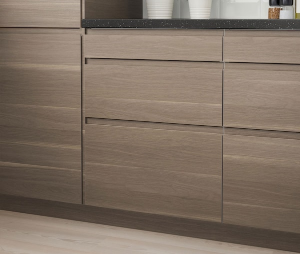A close up of a kitchen cabinet with IKEA VOXTORP walnut effect drawers.