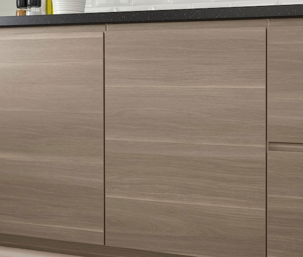 A close up of a kitchen cabinet with IKEA VOXTORP walnut effect doors.