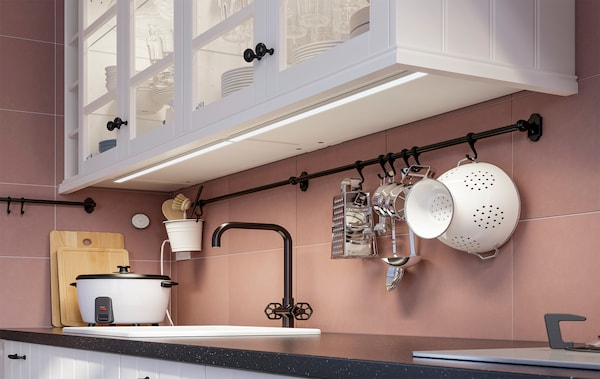 A close up of a kitchen wall cabinet with an OMLOPP lighting strip underneath.