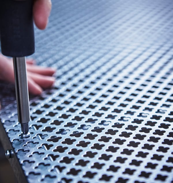 A close-up of a mesh metal sheet being screwed to the back of a IKEA HYLLIS shelving unit.
