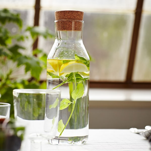 A close-up of a pitcher on a table containing slices of lemon and mint.