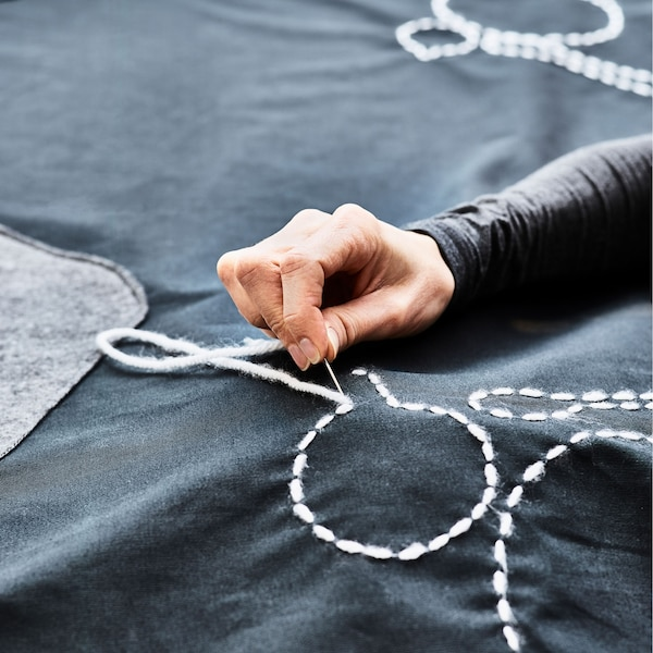A close up of a plate outline being sewn onto a table cloth and an animated gif showing an outdoor table being covered in a table cloth that looks like a play mat with roads