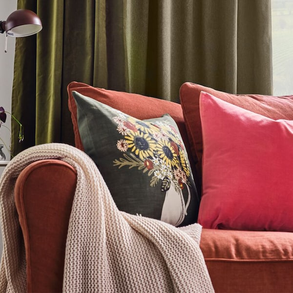 A close up of a red IKEA sofa with decorative cushions and pale throw.