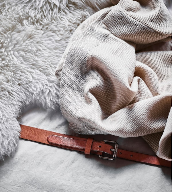 A close-up of a sheepskin and soft throw on seating made from mattresses.