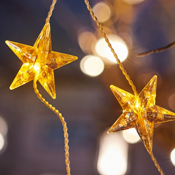 A close-up of a star-shaped gold STRÅLA LED lighting chain hanging from a tree outside.