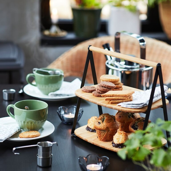 A close up of a table set for afternoon tea with a FULLSPÄCKAD serving tray and STRIMMIG mugs.