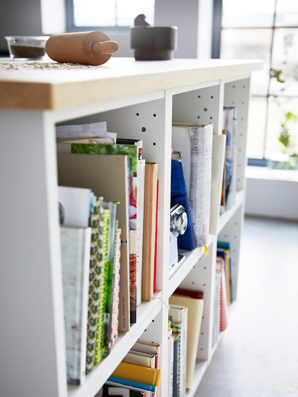 A close-up of a white kitchen island with a wooden countertop showing open cabinets storing cookbooks.