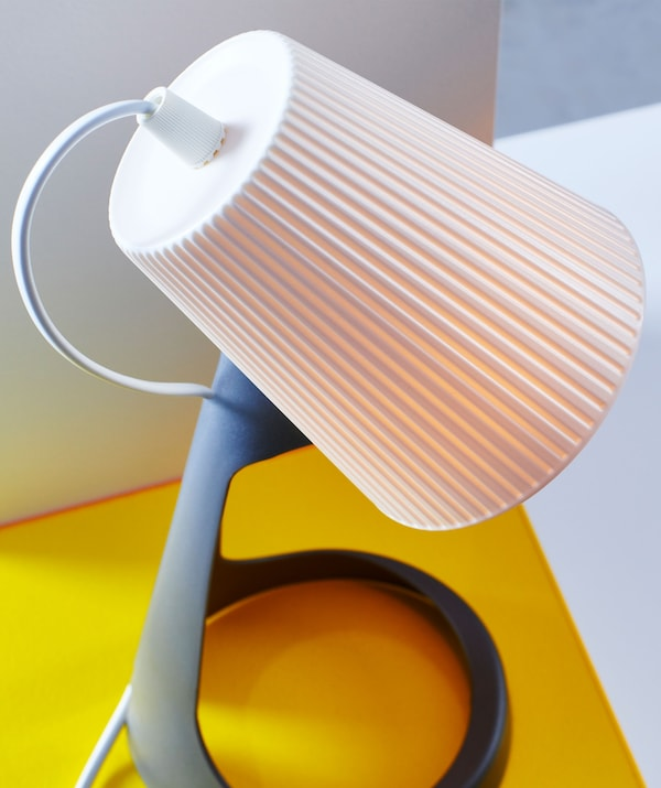 A close-up of a white lampshade on a work lamp.