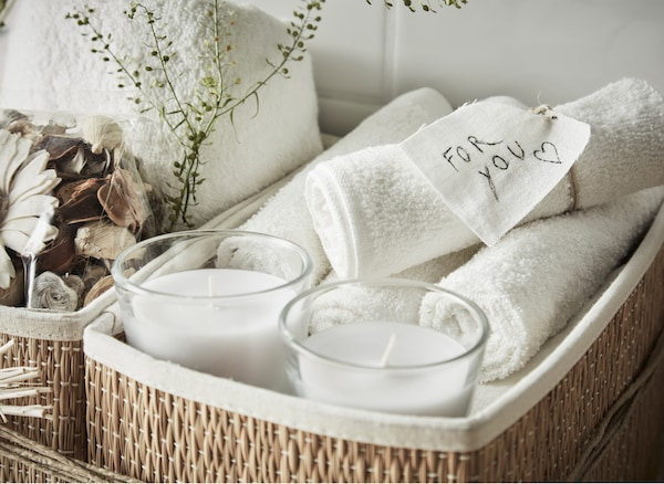 A close-up of an at-home spa gift kit with washcloths and scented candles in a storage basket.