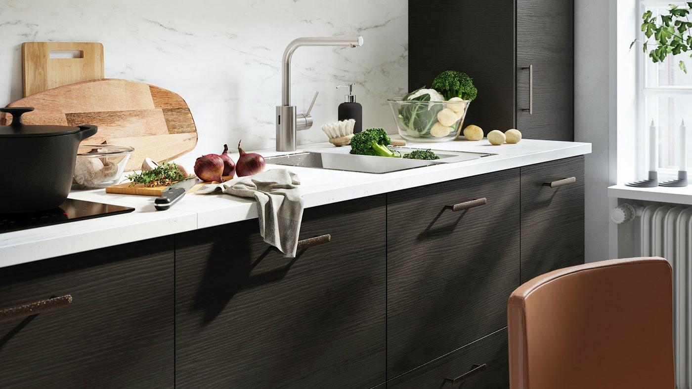 A close up of an IKEA ASKERSUND dark brown kitchen with white worktop and metal, slimline handles.