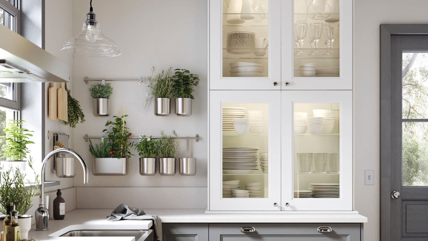 A close up of an IKEA AXSTAD white kitchen cabinet with glass doors, white worktop and black door knobs.