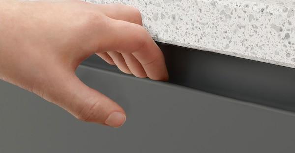 A close up of an IKEA VOXTORP dark grey handleless drawer.
