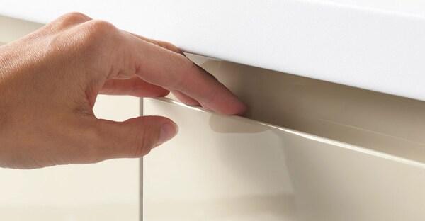 A close up of an IKEA VOXTORP high-gloss light beige handleless drawer.