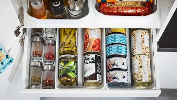 A close-up of an open drawer with cans, tins, and spices organized using VARIERA dividers.