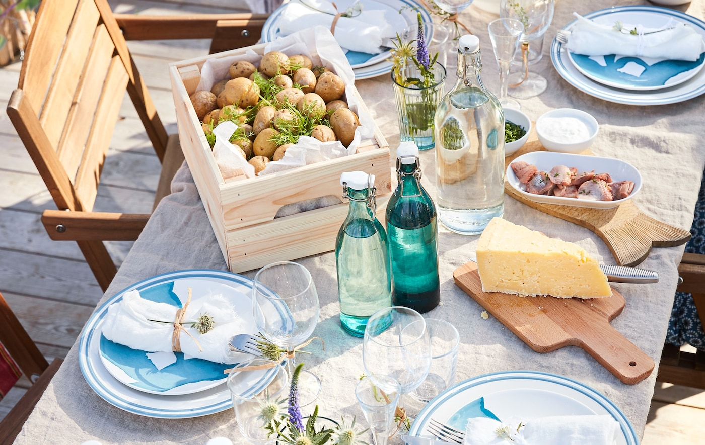 A close up of an outdoor dining table with dinnerware, glasswar, food and drink.