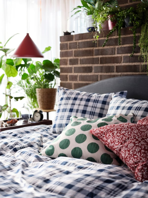 A close-up of an upholstered HAUGA bed, with a checked duvet cover, a spotted green pillow and a flowery red pillow.