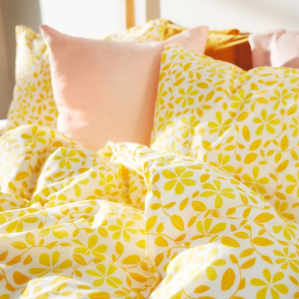 A close-up of bedding with yellow flower pattern and pale pink cushions.