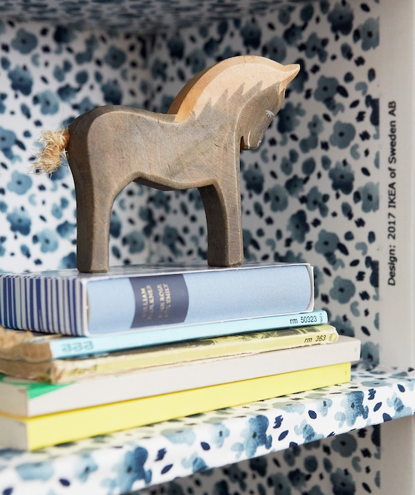 A close-up of books and a horse ornament on a shelf with blue fabric floral pattern.