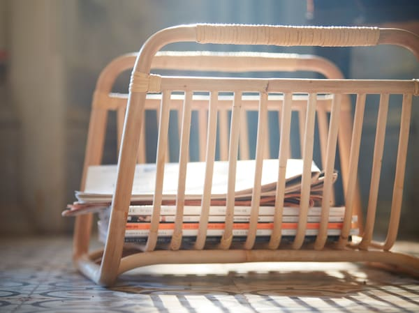 A close-up of BUSKBO magazine stand that's handmade in rattan, placed on the floor storing some magazines.