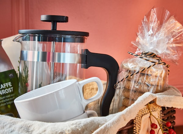 A close-up of coffee gift basket with a coffee maker, mugs and oat biscuits.