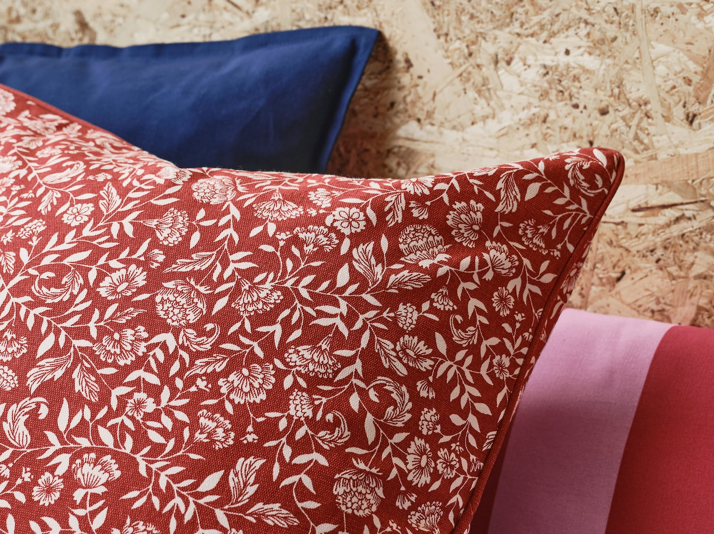 A close-up of EVALOUISE cushion cover featuring a traditional Scandinavian floral pattern in red and white.